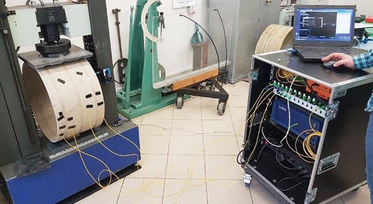 FOT. 1.   Stanowisko badawcze zpróbką rury wprasie mechanicznej iświatłowodami podłączonymi do reflektometru optycznego [6]